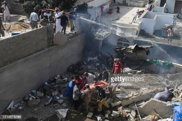Rescue workers move a body from the site after a Pakistan International Airlines aircraft crashed at a residential area in Karachi on May 22 2020 A...