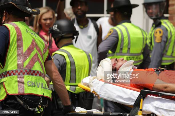 Rescue workers move victims on stretchers after car plowed through a crowd of counterdemonstrators marching through the downtown shopping district...