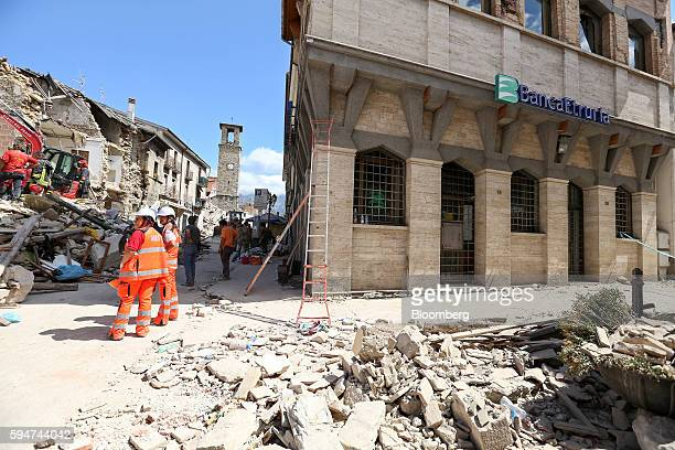 Rescue workers operate close to a branch of Banca Popolare dell'Etruria e del Lazio following an earthquake in Amatrice Italy on Wednesday Aug 24...