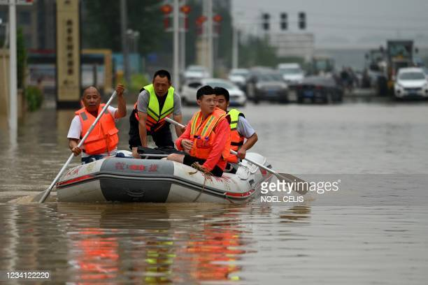 Rescue workers paddle through a flooded street following heavy rains which caused flooding and claimed the lives of at least 33 people earlier in the...