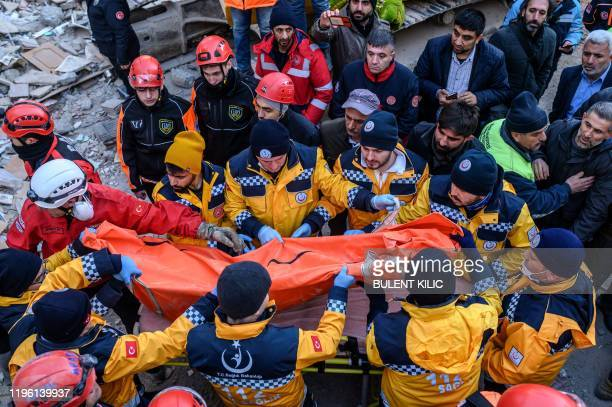 TOPSHOT Rescue workers pass on a body bag with the body of a dead person retrieved from the rubble of a building after an earthquake in Elazig...