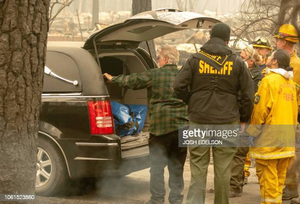 Rescue workers pause after carrying a body from a burned property into a hearse in the Holly Hills area of Paradise California on November 14 2018...