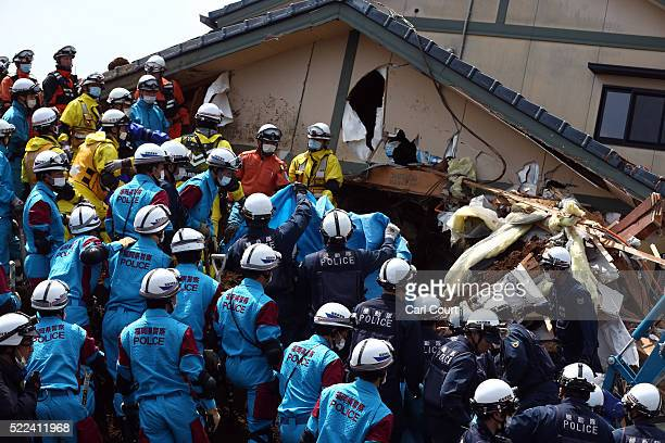 Rescue workers prepare to remove the body of a woman found in a house that was destroyed by a mudslide following an earthquake on April 19 2016 in...
