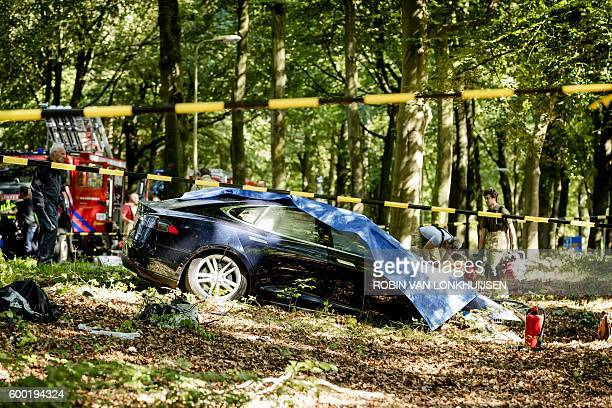 Rescue workers proceed with caution around the spot where a Tesla slammed into a tree in Baarn on September 7 2016 Pioneering US electric car firm...