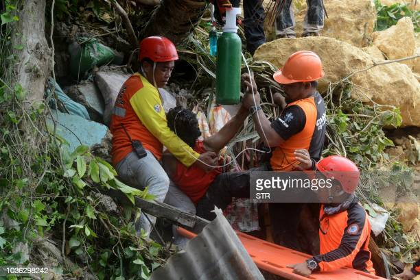 Rescue workers provide first aid to a rescued resident after a landslide triggered by moonson rains hit a village in Naga City, Cebu province in...