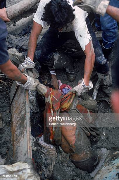 Rescue workers pull a body from mud and rubble after a mudslide, set off by the eruption of the nearby Nevado del Ruiz volcano, claimed over 25,000...