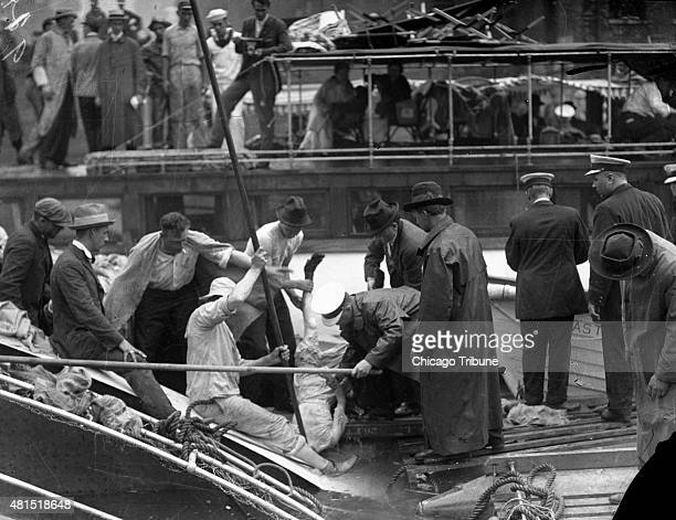 Rescue workers pull a victim from the Chicago River after the SS Eastland rolled over on its side and drowned 844 people July 24, 1915 in Chicago....