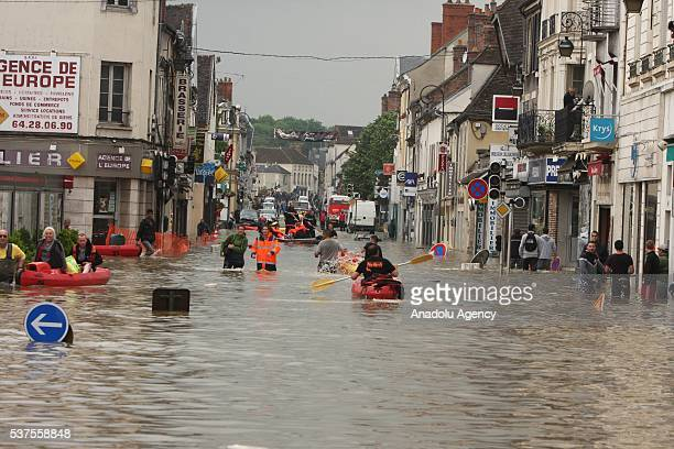 Rescue workers pull residents through a flooded street in Nemours southeast of Paris on June 1 2016 Torrential rain has continued to lash northern...
