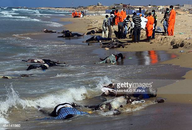 Rescue workers pull the bodies of illegal immigrants onto shore of alQarbole some 60 kilometres east of Tripoli on August 25 2014 after a boat...