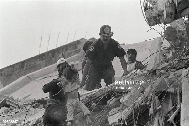 Rescue workers pull the body of a young child from the wreckage of a maternity ward in Mexico City 21 September 1985 following the second massive...