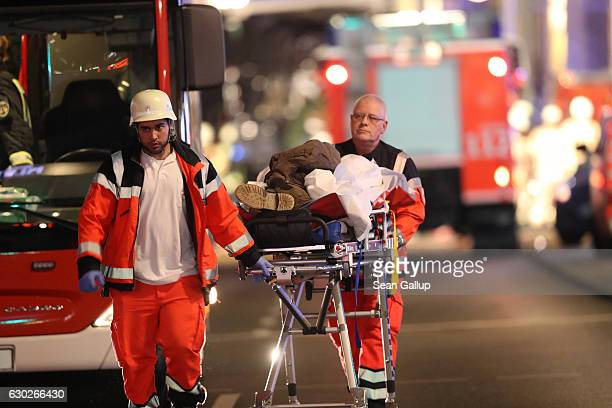 Rescue workers push a person on a stretcher in the area after a lorry truck ploughed through a Christmas market on December 19 2016 in Berlin Germany...