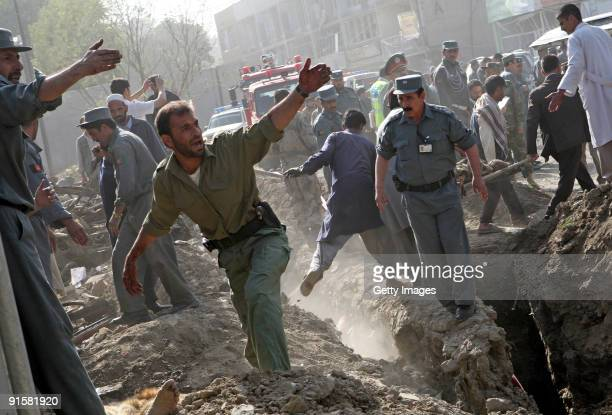 Rescue workers recover a body at the scene of a suicide bombing on October 8, 2009 in Kabul, Afghanistan. The explosion left 12 people dead and over...