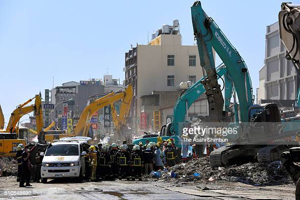 Rescue workers recover a body while heavy equipments are used to demolish the collapsed building on February 13 2016 in Tainan Taiwan Tainan city...