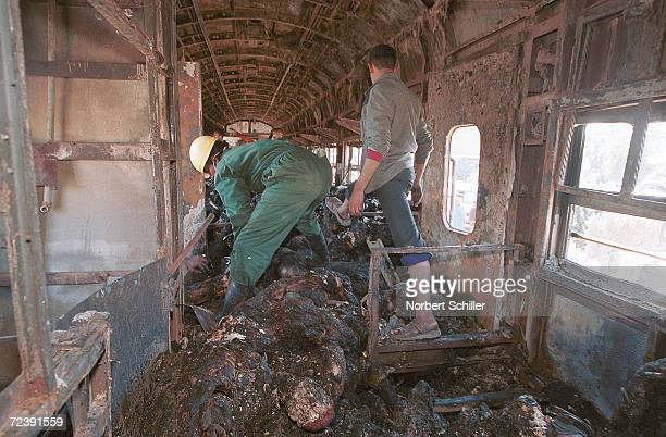 Rescue workers recover bodies from inside the train that caught fire February 20 2002 while heading south from Cairo for the Islamic holidays Over...