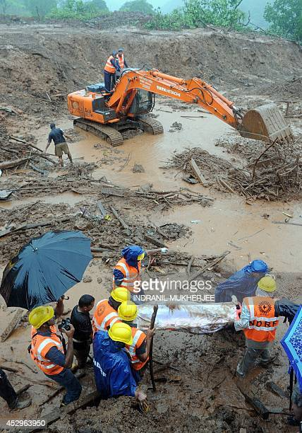 Rescue workers recover the body of a landslide victim as heavy rain falls at the scene in Malin village in Pune district of India's western state of...