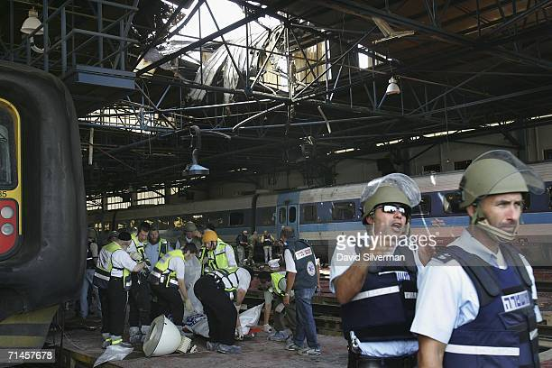 Rescue workers remove a victim's body from the scene where a Hezbollah missile broke through the roof and exploded in a railway depot July 16 2006 in...