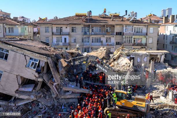 Rescue workers remove corpses from the rubble of a building after an earthquake in Elazig eastern Turkey on January 26 2020 Rescue workers raced...