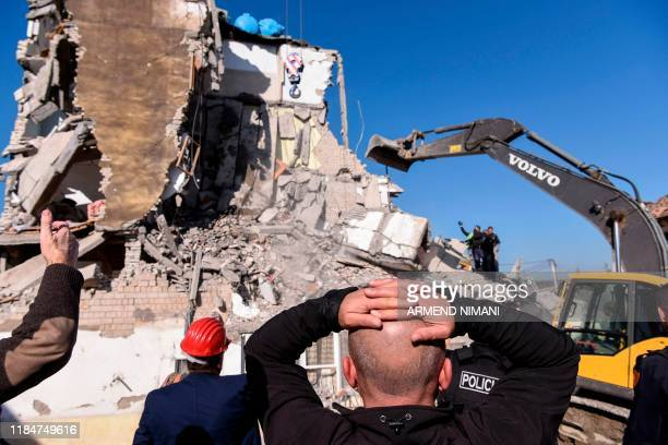 Rescue workers remove debris from a collapsed building in Thumane, northwest of capital Tirana, after an earthquake hit Albania, on November 26,...