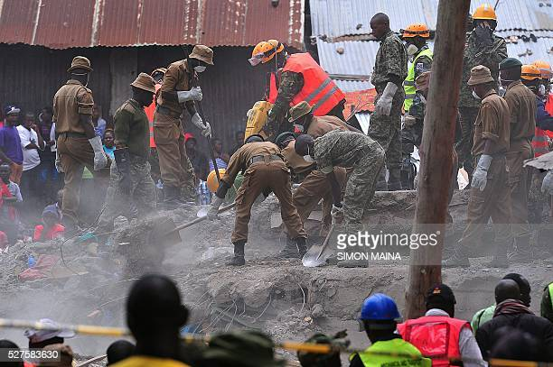 Rescue workers remove debris from the rubble of the sixstorey building that collapsed killing 23 people in Nairobi's suburb of Huruma on May 3 2016...