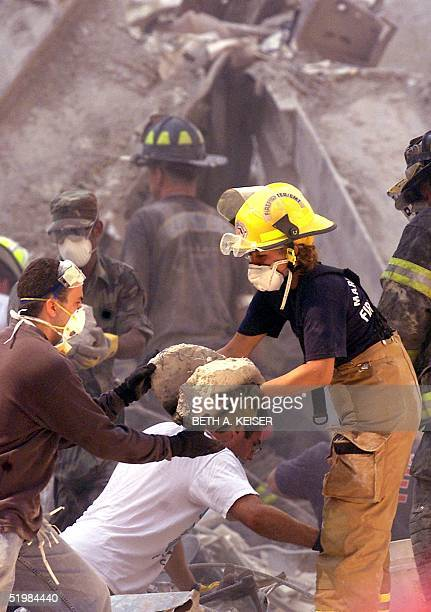 Rescue workers remove debris from the rubble of the World Trade Center 13 September 2001 in New York, two days after terrorist attack.