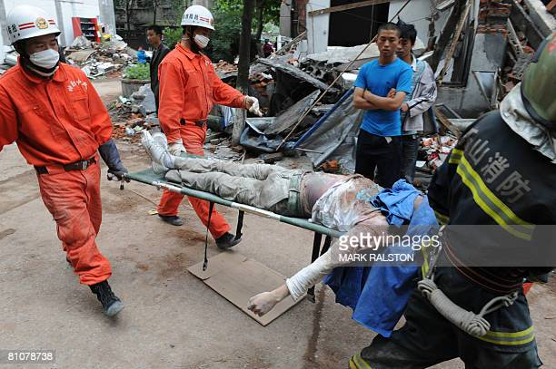 Rescue workers remove the body of a child when a high school collapsed after a 78 magnitude earthquake hit the town of Hanwang in Sichuan Province on...