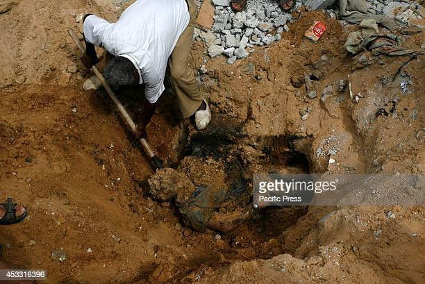 Rescue workers remove the body of a Palestinian man from the rubble following an earlier Israeli air strike in Rafah in the Southern Gaza Strip...