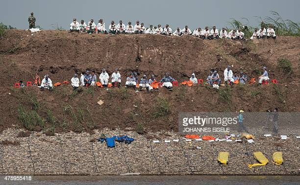 Rescue workers rest next to empty stretchers on the river bank next to the turned around capsized passenger ship as it is lifted by cranes in the...