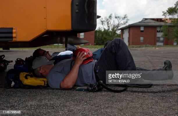Rescue workers rest under a bus in Trotwood Ohio after powerful tornadoes ripped through the US state overnight causing at least one fatality and...