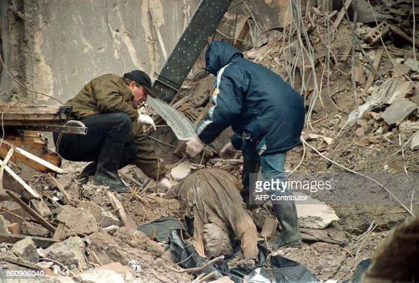 Rescue workers retrieve a body from the rubble of the Serbian television headquarters in Belgrade 25 April 1999 three days after the building was...