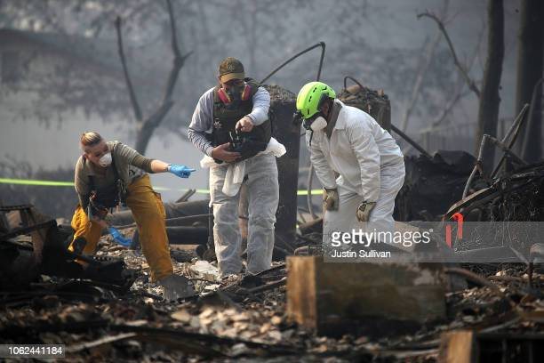 Rescue workers search an area where they discovered suspected human remians in a home destroyed by the Camp Fire on November 16 2018 in Paradise...