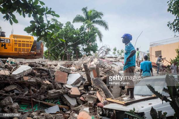 Rescue workers search for survivors among the debris of collapsed houses after a 7.2-magnitude earthquake struck Haiti on August 19, 2021 in Les...