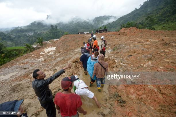 Rescue workers search for survivors at the site of a landslide triggered by heavy rain in Sukabumi West Java province on January 1 2019 Rescuers are...