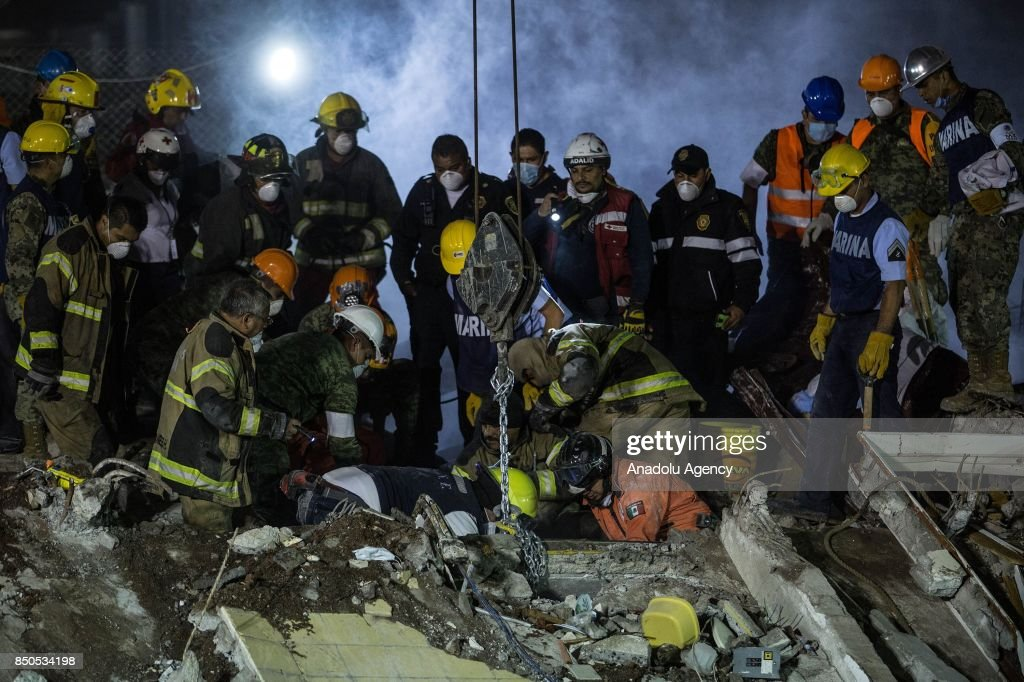 Rescue workers search for the trapped citizens over the collapsed buildings after a powerful magnitude 7.1 earthquake that hit Mexico City, Mexico on September 21, 2017.