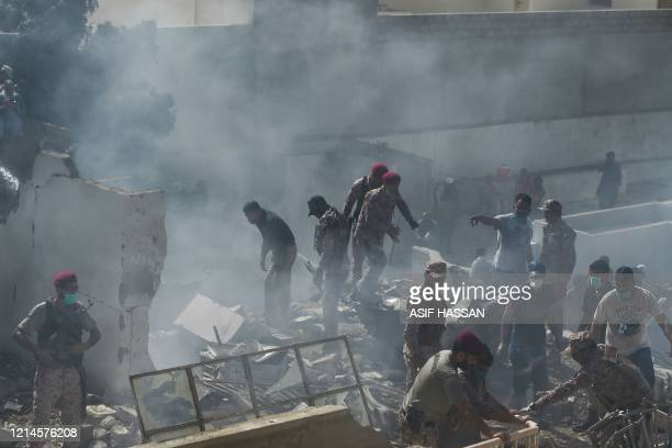 Rescue workers search for victims at the site after a Pakistan International Airlines aircraft crashed at a residential area in Karachi on May 22...