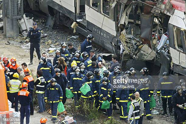 Rescue workers search the surroundings after a train exploded near the Atocha train station in Madrid 11 March 2004 More than 170 people were killed...