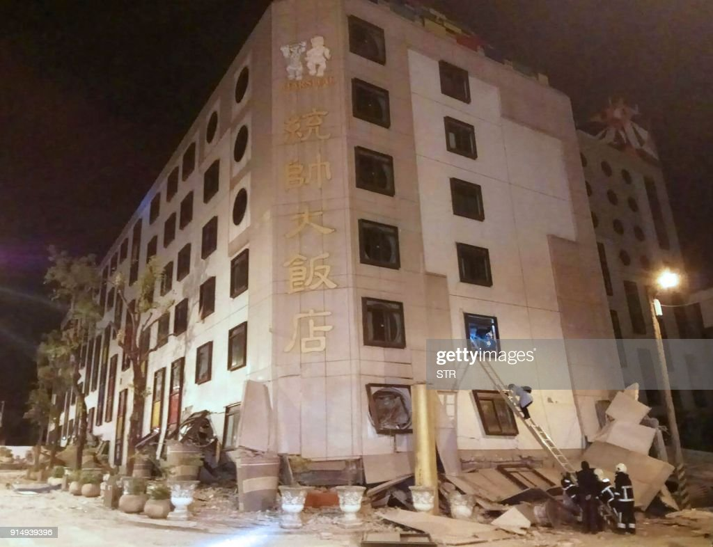 TOPSHOT - Rescue workers search through rubble outside the Marshal Hotel in Hualien, eastern Taiwan early February 7, 2018, after a strong earthquake struck the island. A hotel on the east coast of Taiwan has collapsed after a 6.4-magnitude earthquake, the government said. / AFP PHOTO / STR / Taiwan OUT