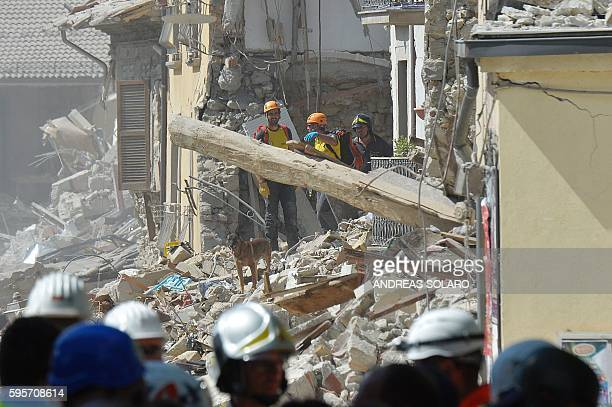 TOPSHOT Rescue workers search through the rubble of an earthquake damaged building in the central Italian village of Amatrice on August 26 two day...
