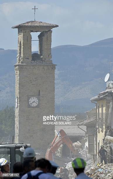 Rescue workers search through the rubble of an earthquake destroyed building in front of a damaged bell-tower in the central Italian village of...