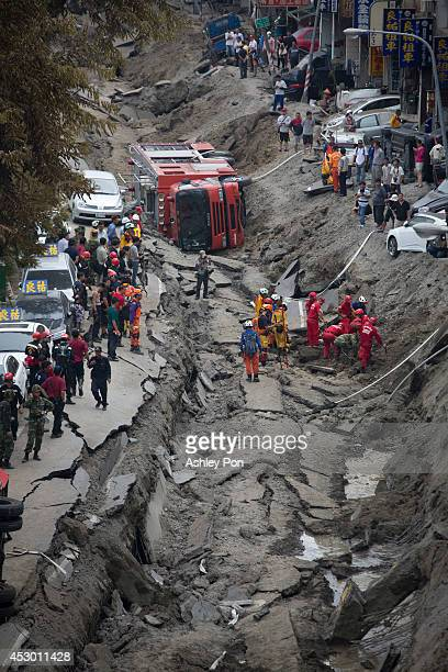 Rescue workers search through the site of the damaged road after several gas explosions in southern Kaohsiung on August 1, 2014 in Kaohsiung, Taiwan....