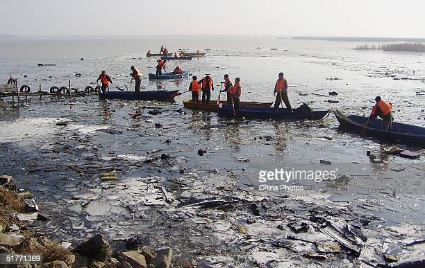 Rescue workers search through the wreckage of a China Eastern commuter plane which crashed in Inner Mongolia on a frozen lake in Nanhai Park on...