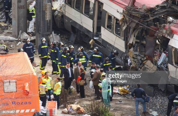Rescue workers search through the wreckage of a commuter train March 11, 2004 after it was devastated by a bomb blast during the morning rush hour in...