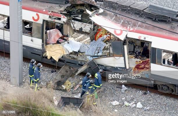 Rescue workers search through the wreckage of a commuter train March 11 2004 after it was devastated by a bomb blast during the morning rush hour in...