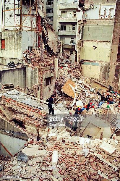 Rescue workers sift through the rubble at the site of a carbombing at the Asociacion Mutual Israelita Argentina Jewish Community Center in Buenos...