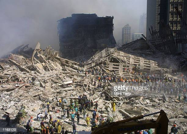 Rescue workers sift through the wreckage of the World Trade Center September 13, 2001 in New York City, two days after two hijacked airplanes slammed...