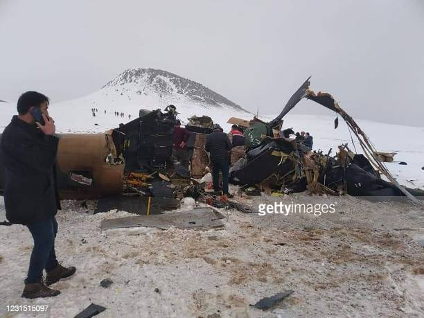 Rescue workers, soldiers and civilians walk around the wreckage of a military helicopter that crashed on March 4 near the Turkish eastern city of...
