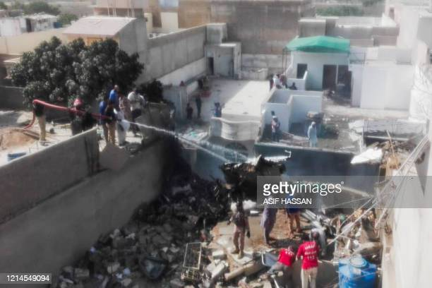 Rescue workers spray water on the part of a Pakistan International Airlines aircraft after it crashed at a residential area in Karachi on May 22 2020...