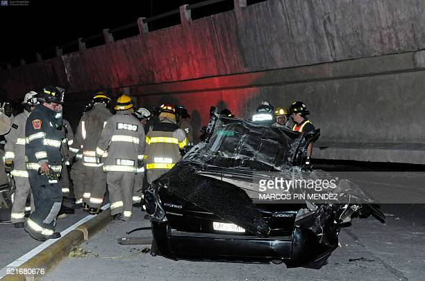 Rescue workers stand before a destroyed car after the collapse of a bridge in an earthquake April 16 2016 in Guayaquil Ecuador At least 28 people...