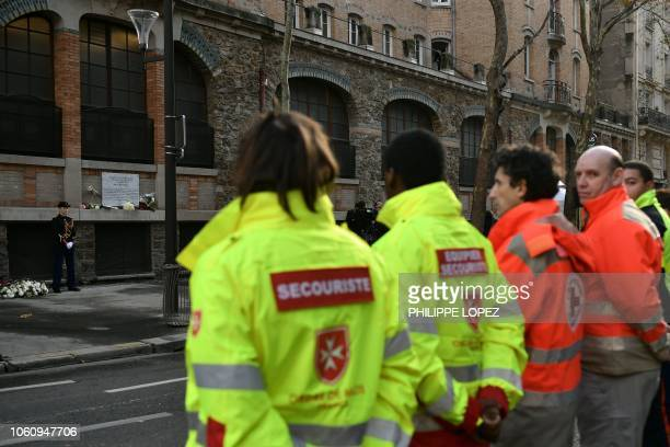 Rescue workers stand in front of a commemorative plaque at La Belle Equipe restaurant prior to a ceremony marking the third anniversary of the Paris...