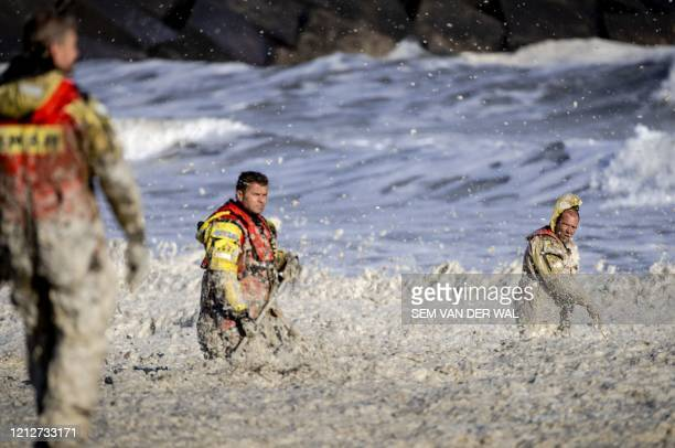 Rescue workers stand in rough waters during the resumed search for missing water sports participants in The North Sea at Scheveningen, The...