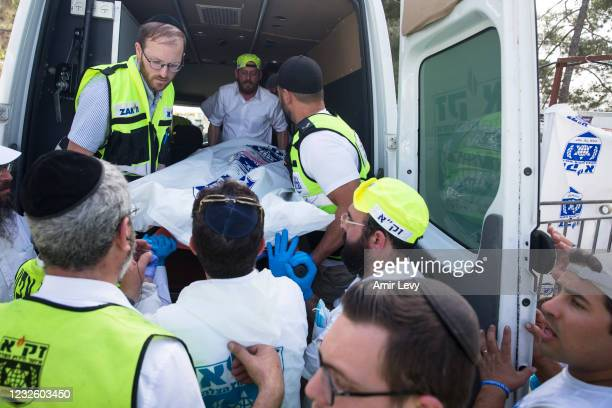 Rescue workers take a dead body into an ambulance after dozens were killed in a crush at a religious festival in Mount Meron on April 30, 2021 in...